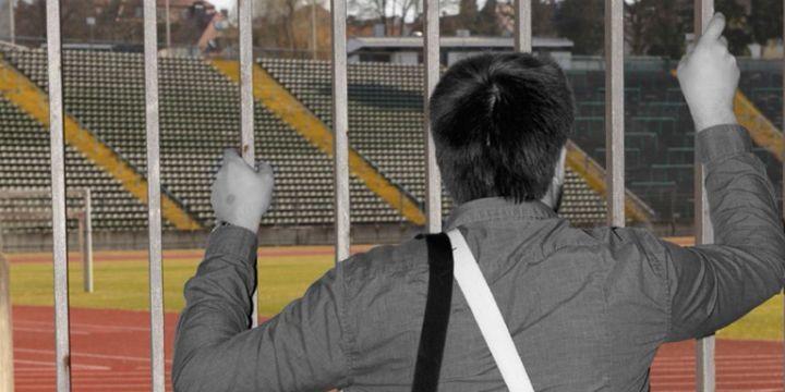 Ein Journalist steht vor einem verschlossenen Stadiontor