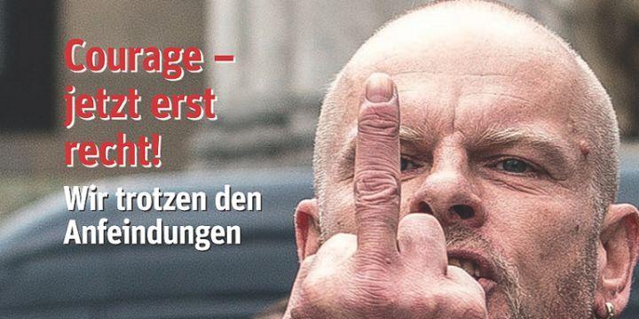 Aggressiv blickender Mann zeigt dem Fotografen den Mittelfinger