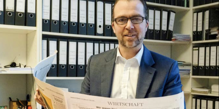 Lächelnder Mann, der in einem Büro den Wirtschaftsteil der Süddeutschen Zeitung liest