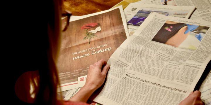 """Frau, die einen Zeitungsartikel mit dem Titel """"Warum Zeitung kein Selbstbedienungsladen ist"""" liest"""
