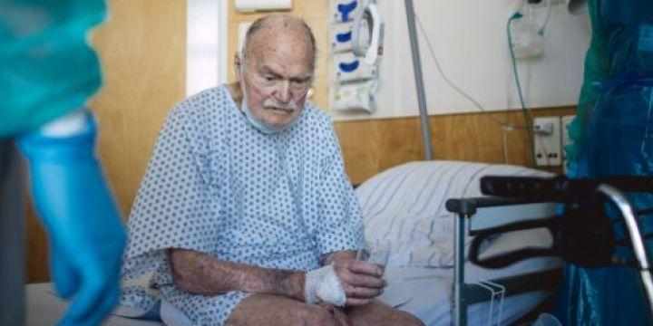 Älterer Patient sitzt auf seinem Krankenhausbett