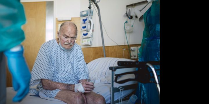Alter Mann sitzt in Patientenkleidung auf einem Krankenhausbett