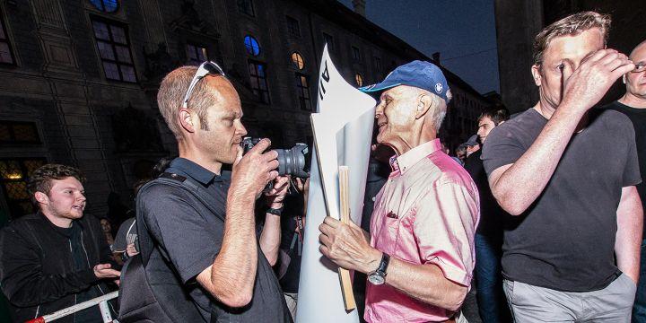 Der Teilnehmer einer Pegidademonstration in München hindert einen Journalisten beim fotografieren